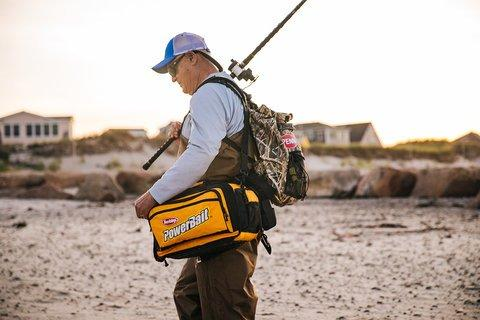 Angler carrying supplies on beach