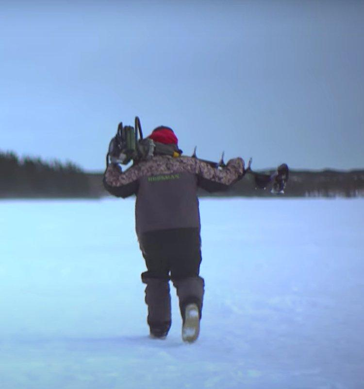 Screenshot of ice fishing video showing angler walking across ice with drill