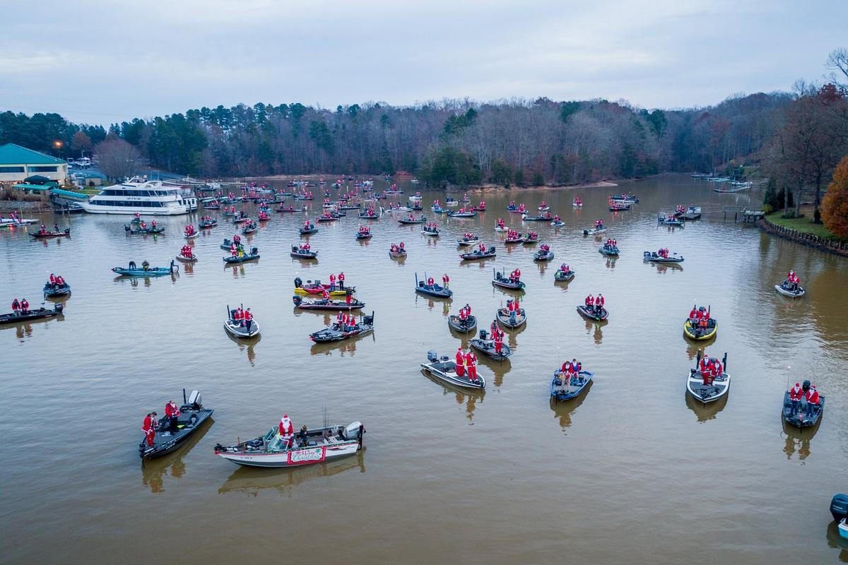 Lake full of boats containing anglers dressed as Santa