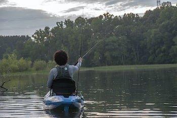 Angler reeling in fish from boat