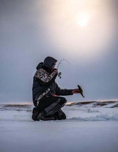Ice fishing angler retrieving catch
