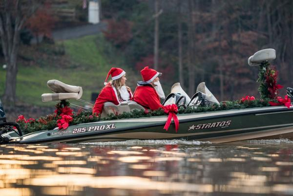 Two anglers in decorated Christmas boat dressed as Santa Claus and Mrs. Claus