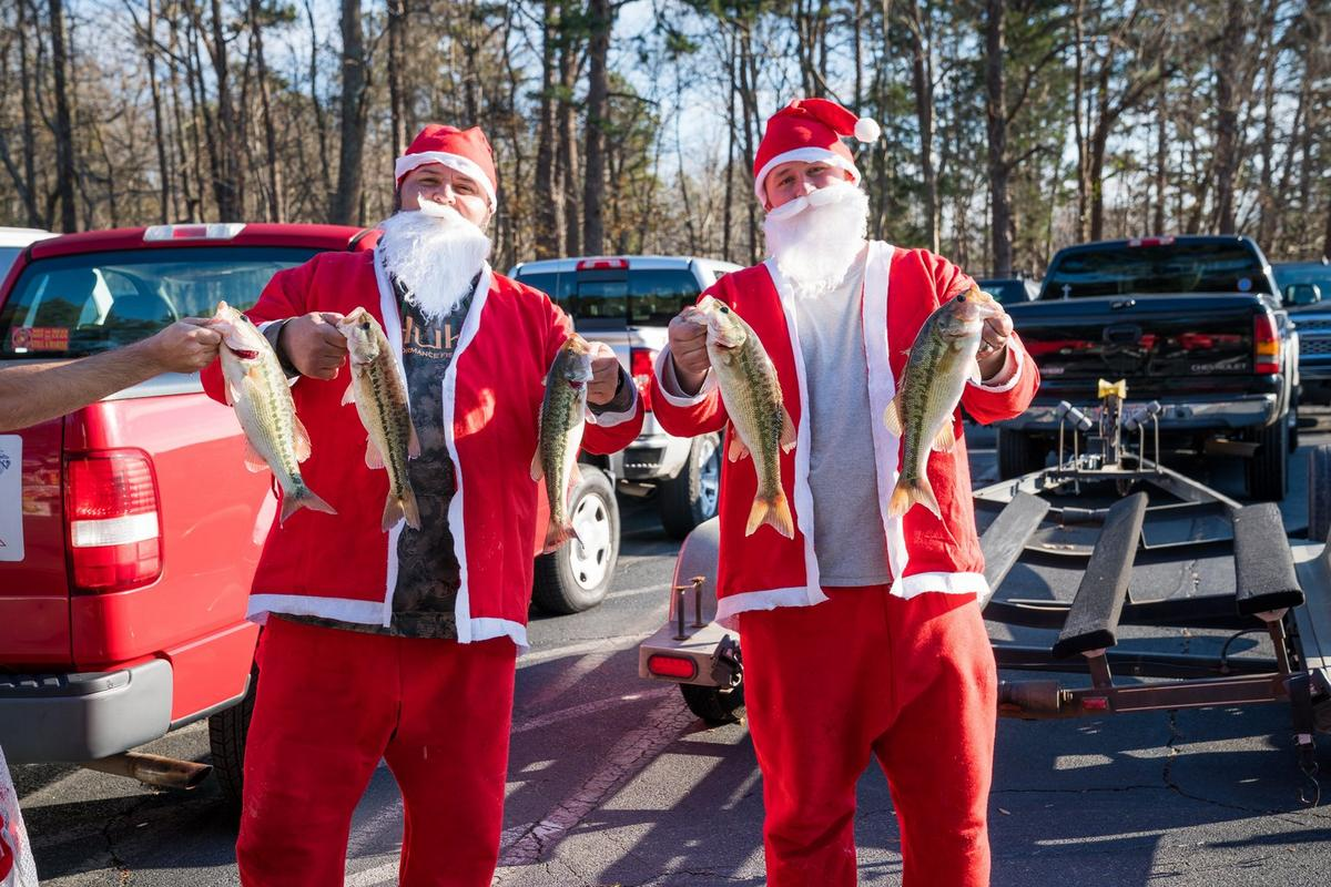 Two anglers dressed as Santa proudly holding up their catches