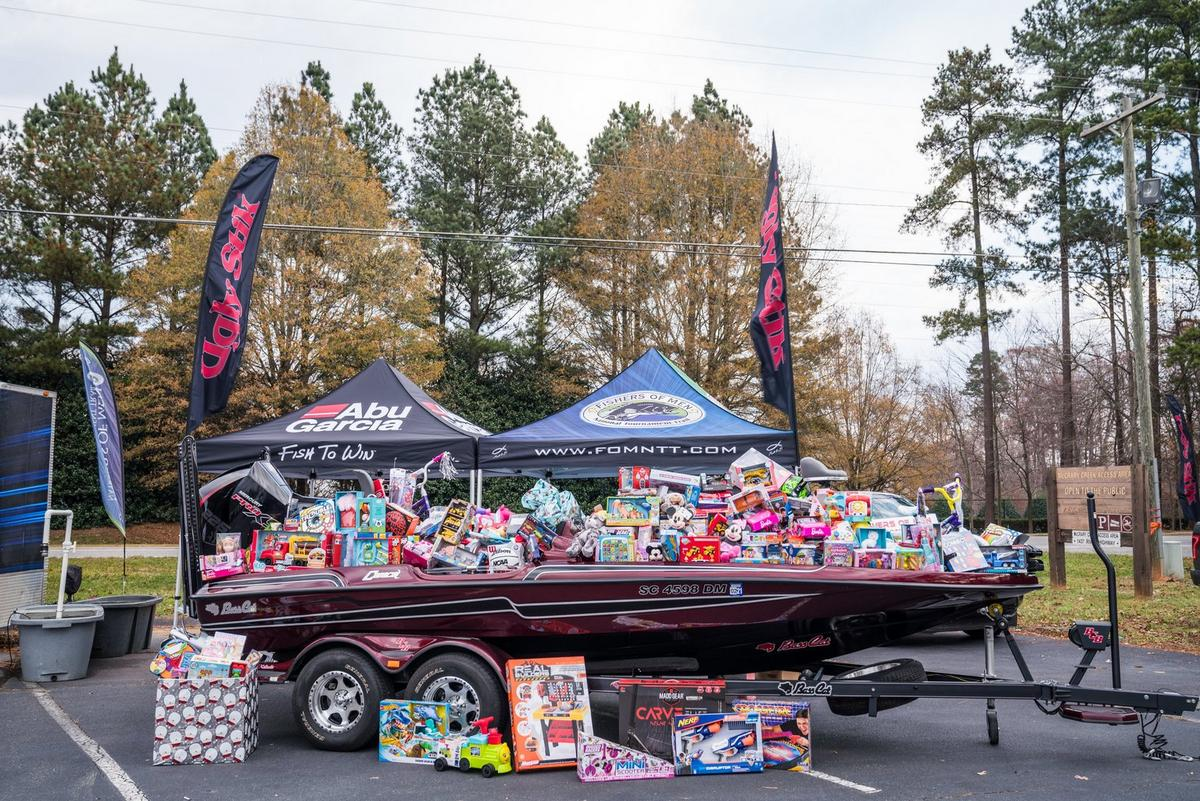 Boat full of gifts for children surrounded by Ugly Stik banners and tents for Abu Garcia and Fishers of Men
