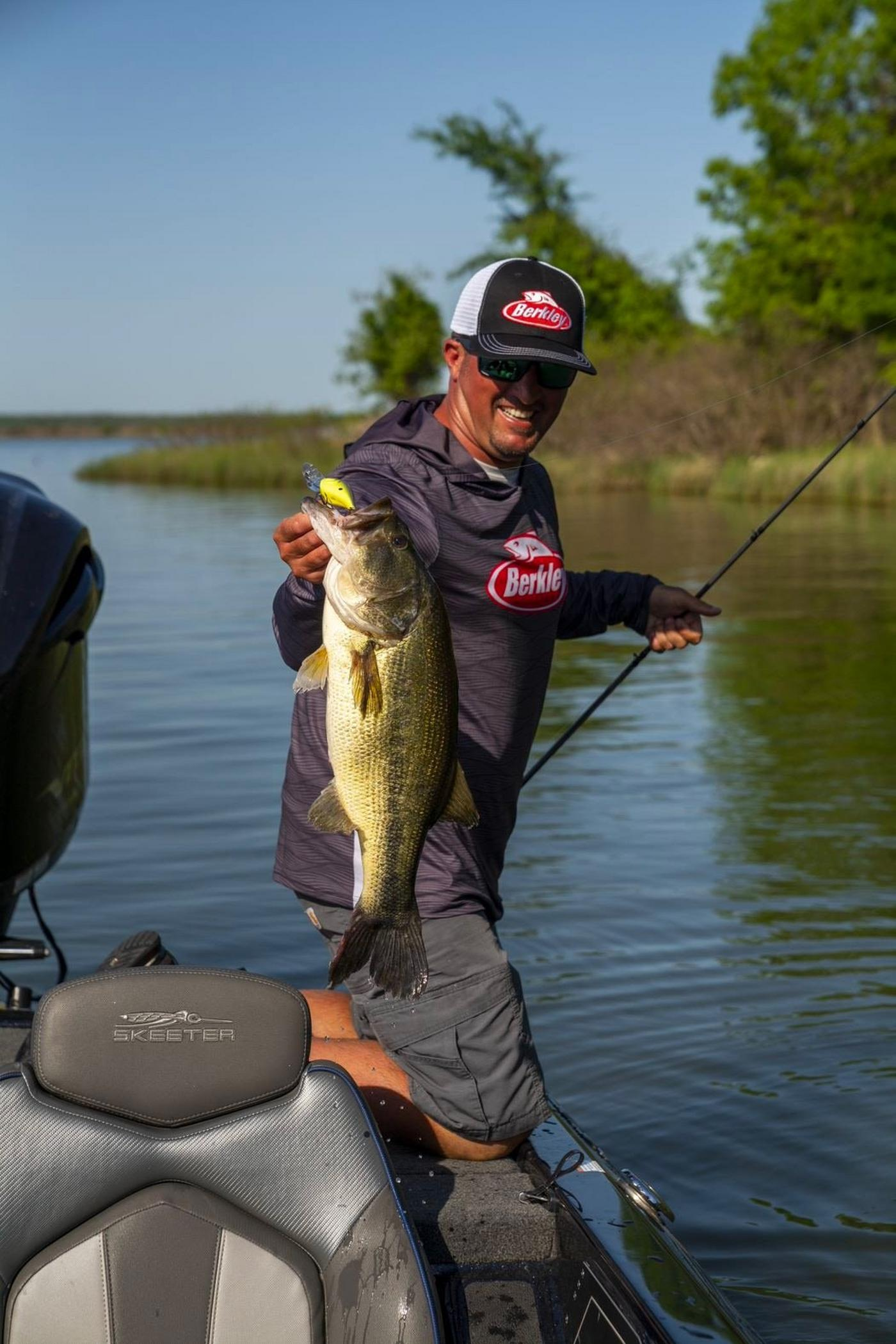 Angler in Berkley gear smiling and holding largemouth bass