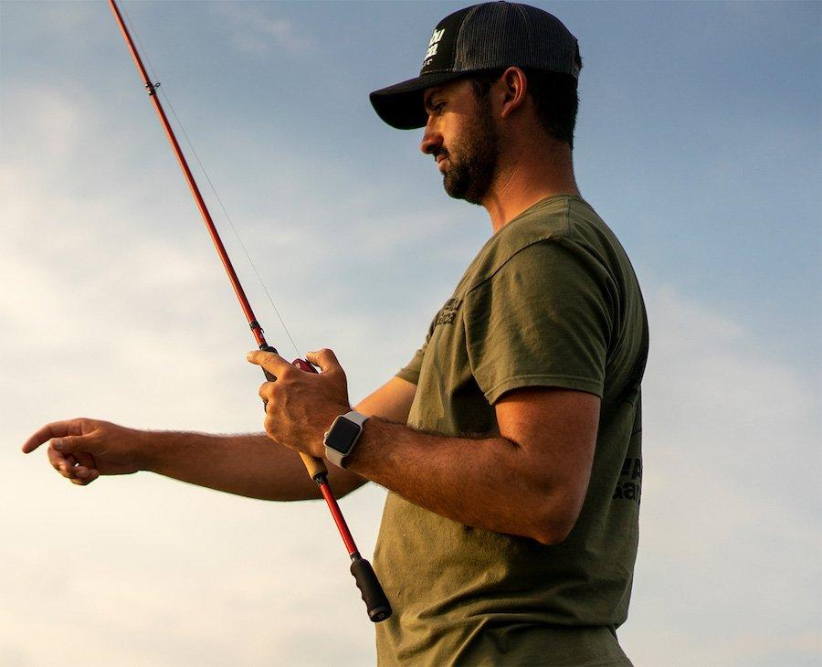 Angler holding rod and pointing at water