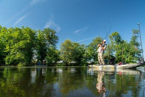 Angler standing on kayak reeling in fish