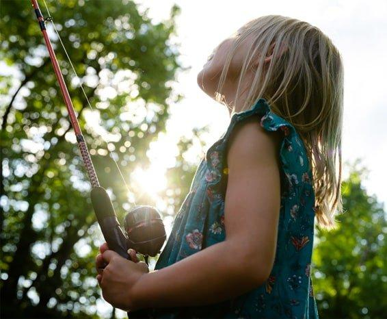 Young girl holding fishing rod and looking toward the sky
