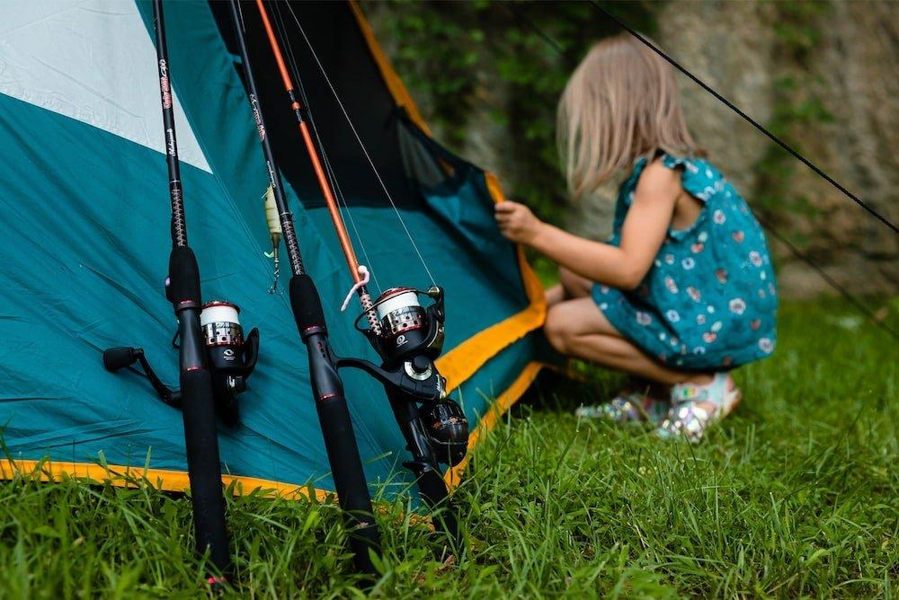 Little girl zipping up tent with fishings rods leaned against it
