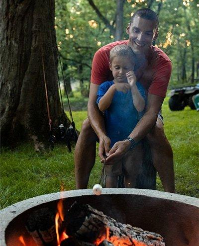 Father and daughter roasting a marshmallow over a fire