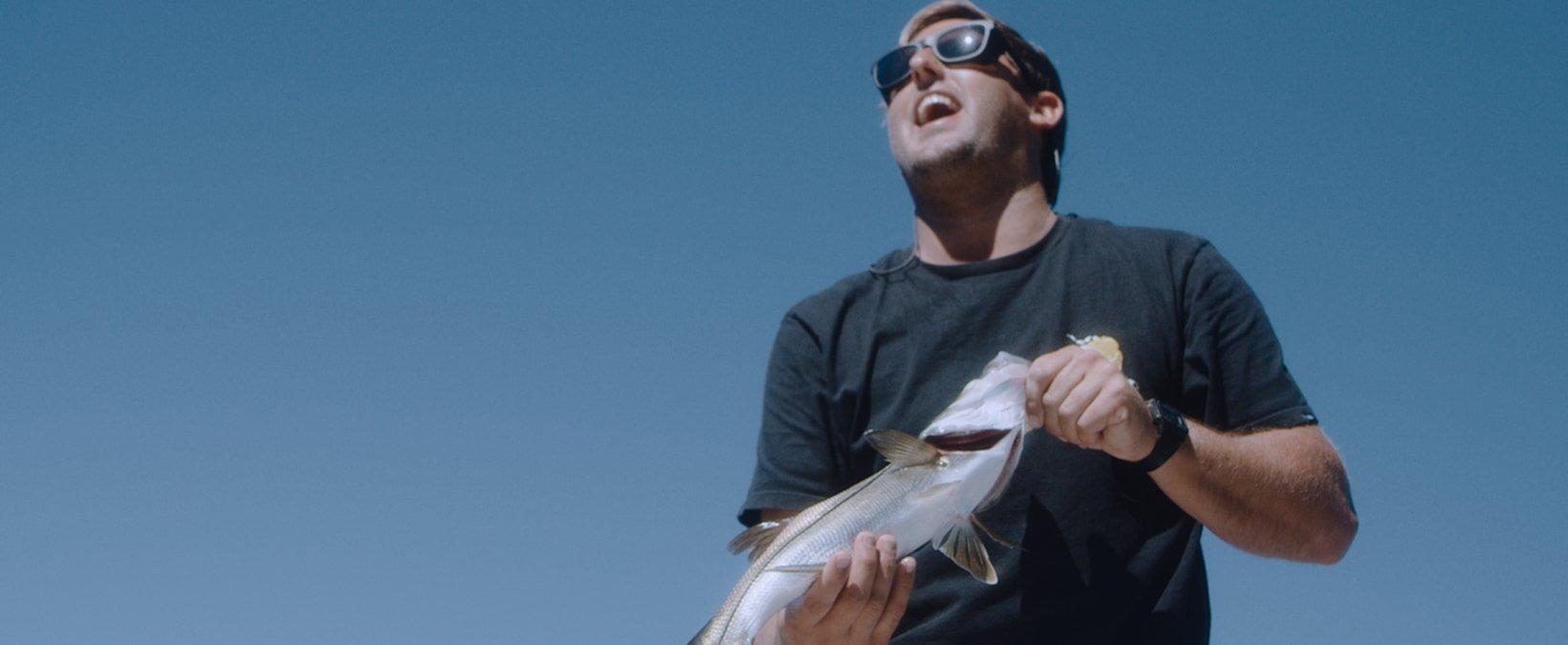 Screenshot of Justin Quintal video showing him holding a fish